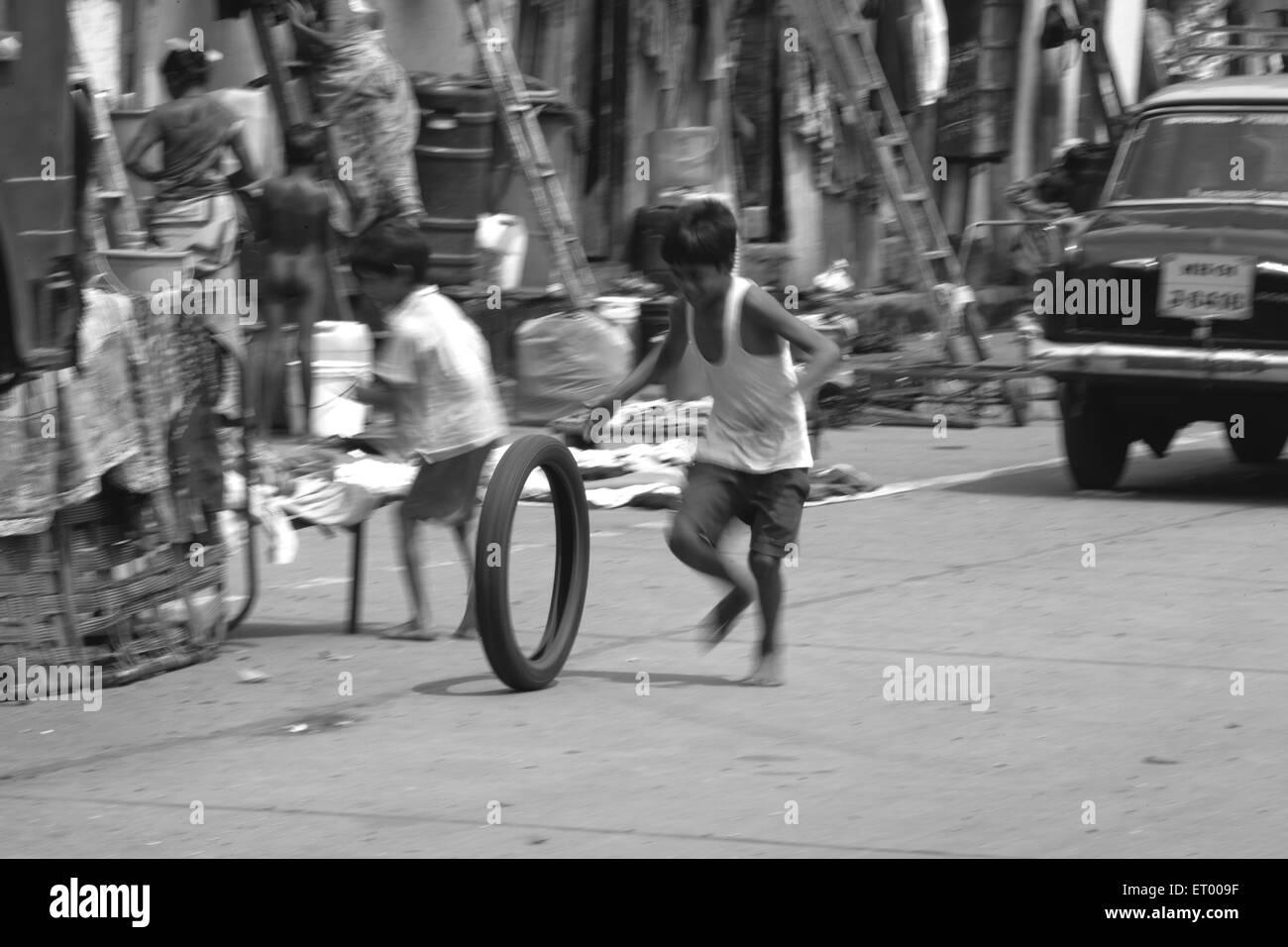 Boy playing with tire Byculla slums N M Joshi Road Bombay Mumbai Maharashtra India - Stock Image
