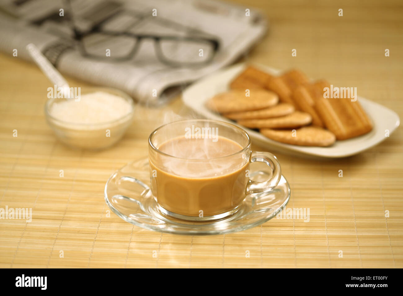 Cup of hot tea with sugar ; biscuits ; newspaper and spectacle - Stock Image