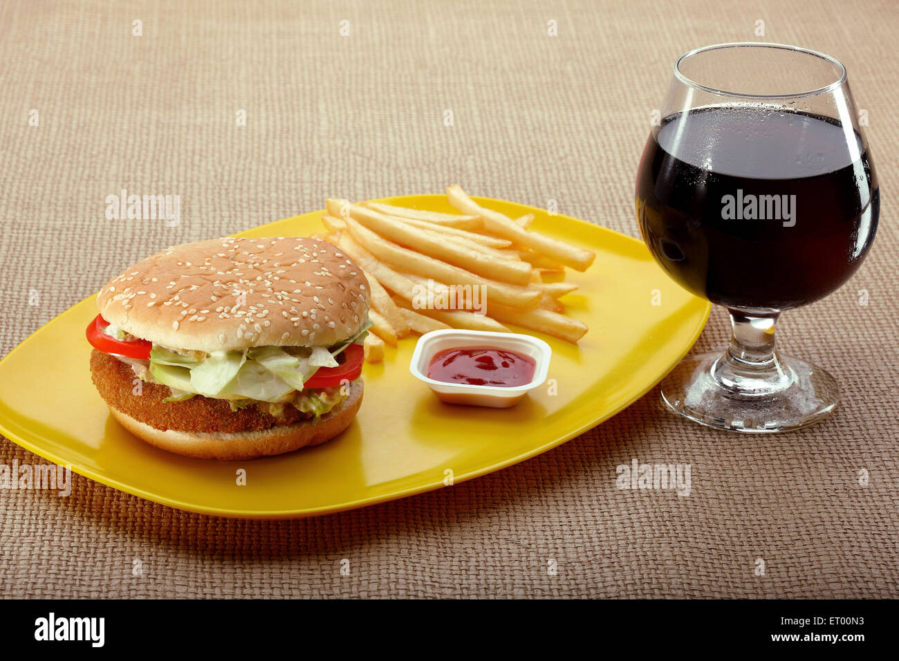 Fast food vegetarian burger with french fries with sauce and cola ; India - Stock Image