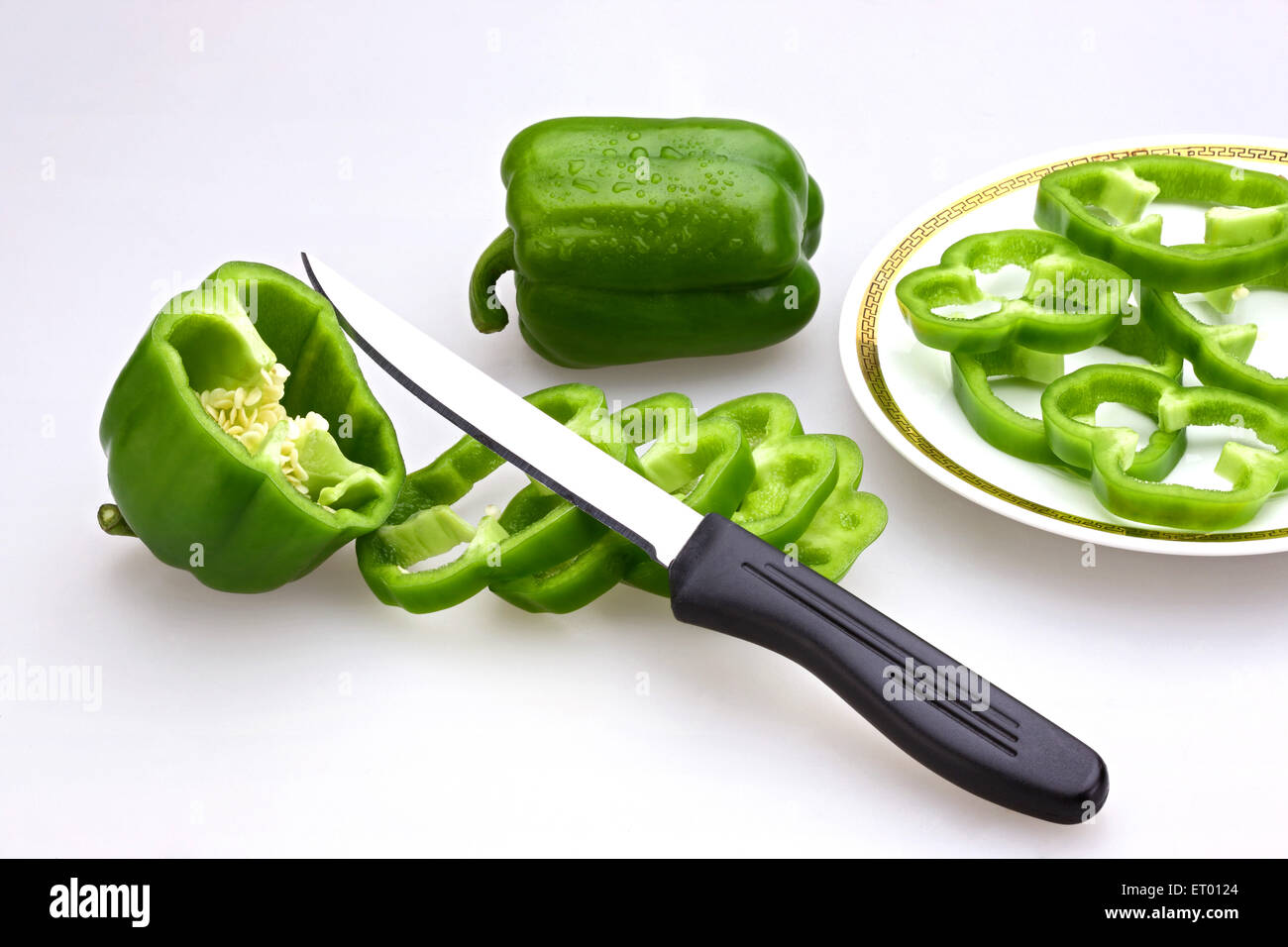 Knife with slices of Green Capsicums Latin Capsicum Annuum on a plate ; salad ; India - Stock Image