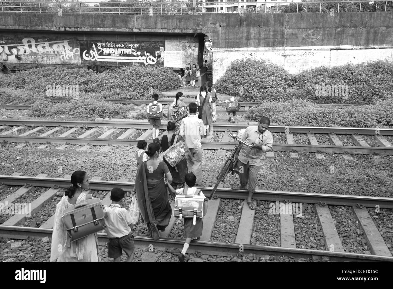 Women with children crossing railway line at Islampura slum ; Wadala ; Bombay Mumbai ; Maharashtra ; India - Stock Image