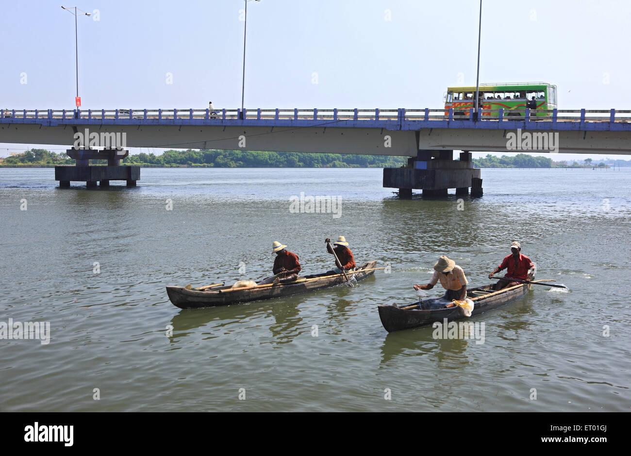 Fishing boats moving in water with connecting bridge ; Yipin island ; Kerala ; India - Stock Image
