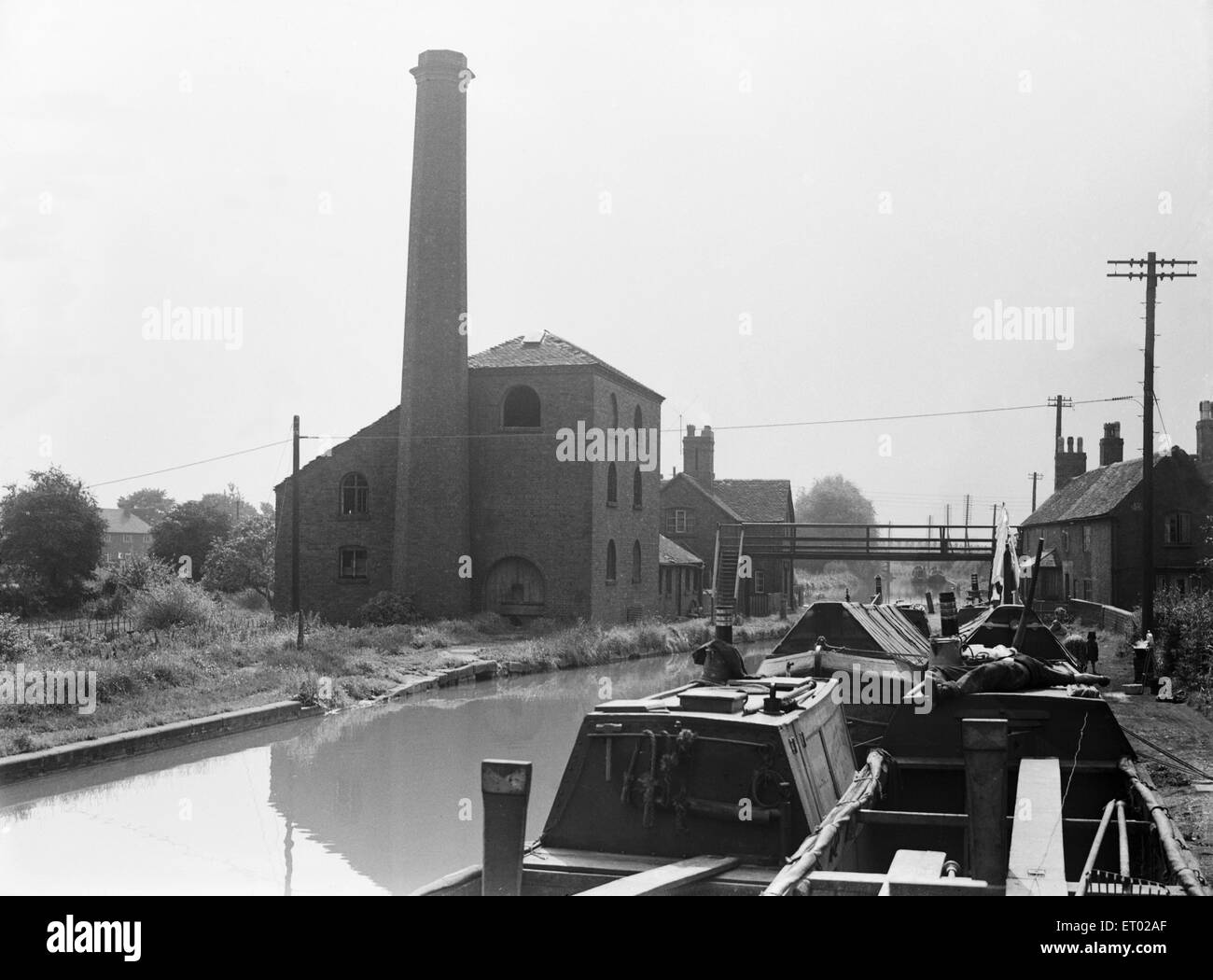 Canal boat captain asleep on the deck of his boat at Hawkesbury Pump house at the junction of the Coventry and Oxford - Stock Image