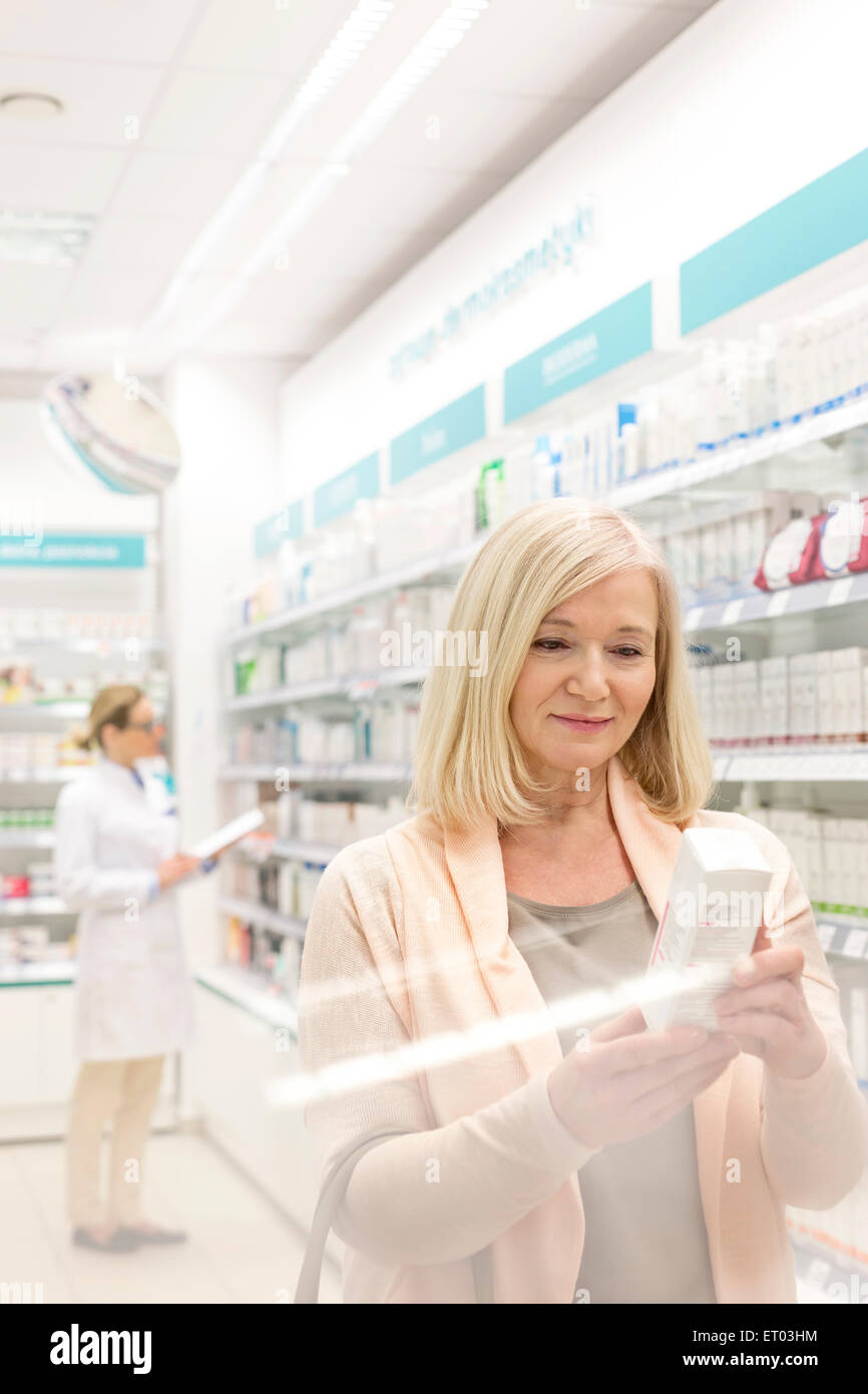 Customer reading label on box in pharmacy - Stock Image