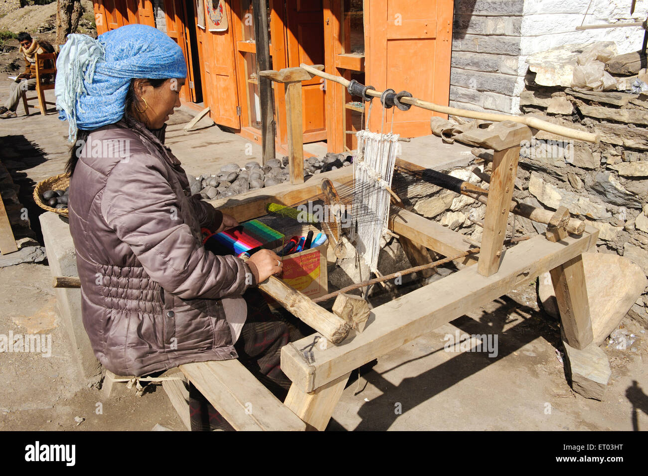 Woman weaving woollen on handloom ; Muktinath ; Nepal NO MR - Stock Image