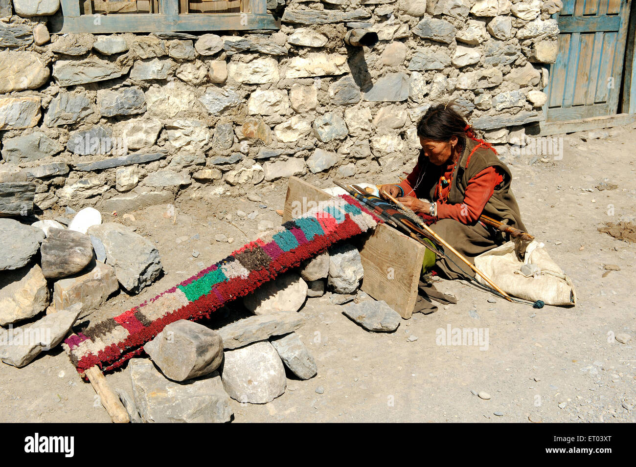 Woman weaving colourful woollen clothes ; Kagbeni ; Nepal NO MR - Stock Image