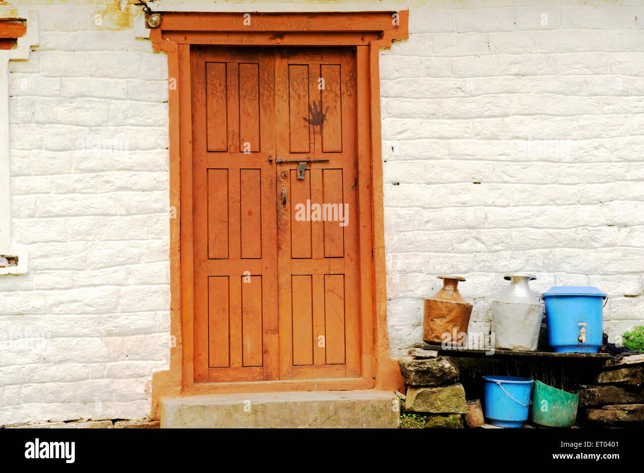 Utensil at wooden door ; Kopchepani ; Nepal - Stock Image