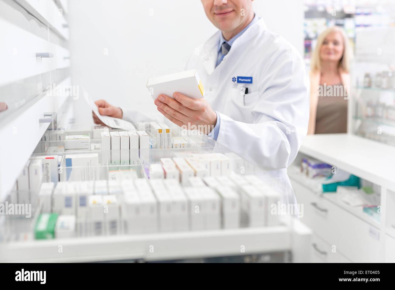 Pharmacist filling prescription in pharmacy - Stock Image