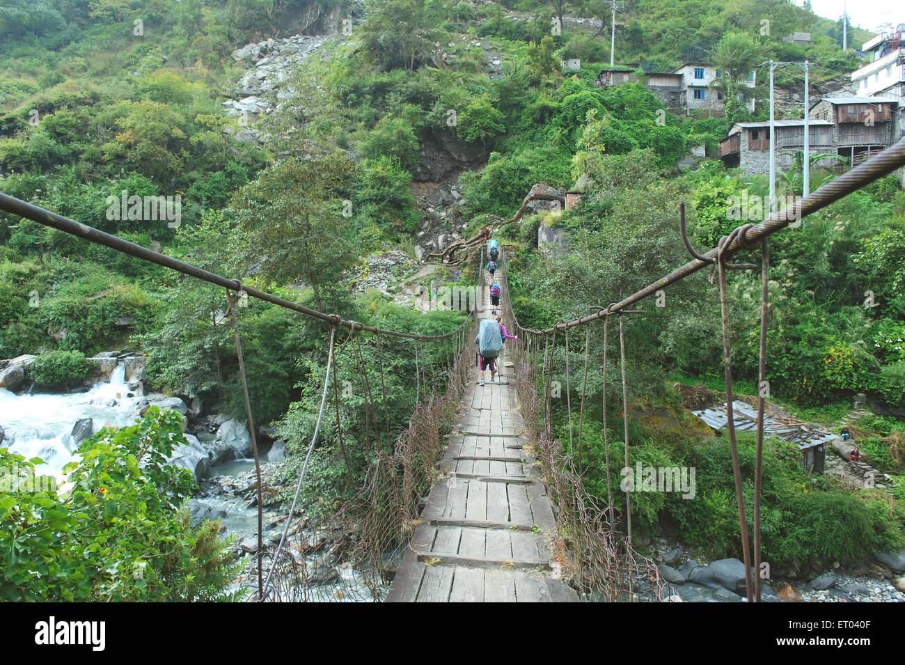 Trekker crossing river ; Tatopani ; Nepal - Stock Image