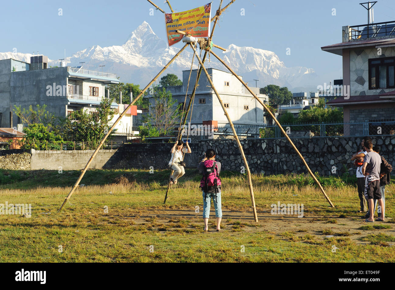 Tourist swinging and snow peaks ; Pokhara ; Nepal - Stock Image