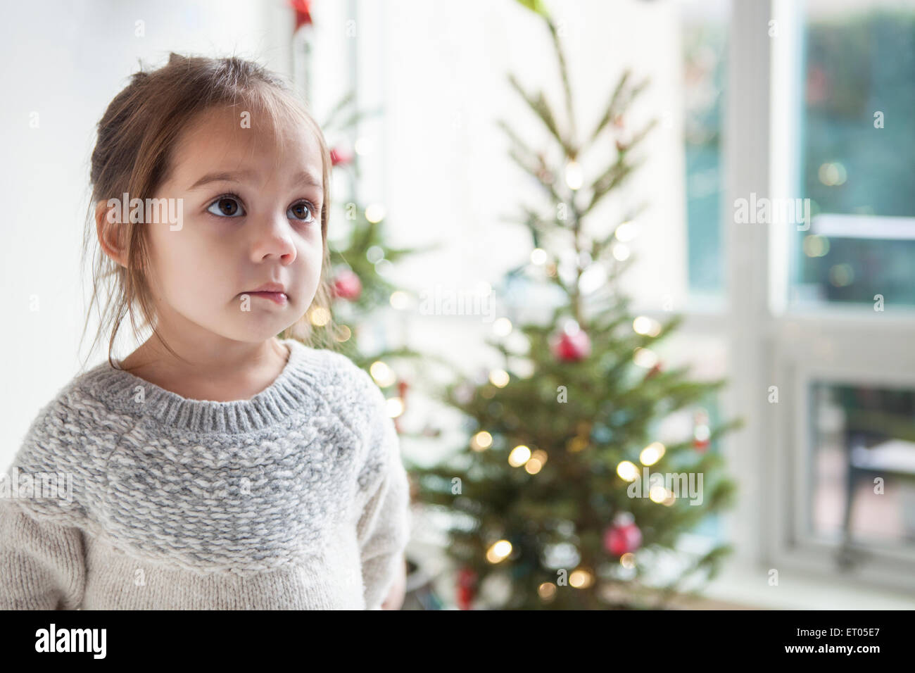 Wide-eyed girl looking up in front of Christmas tree - Stock Image