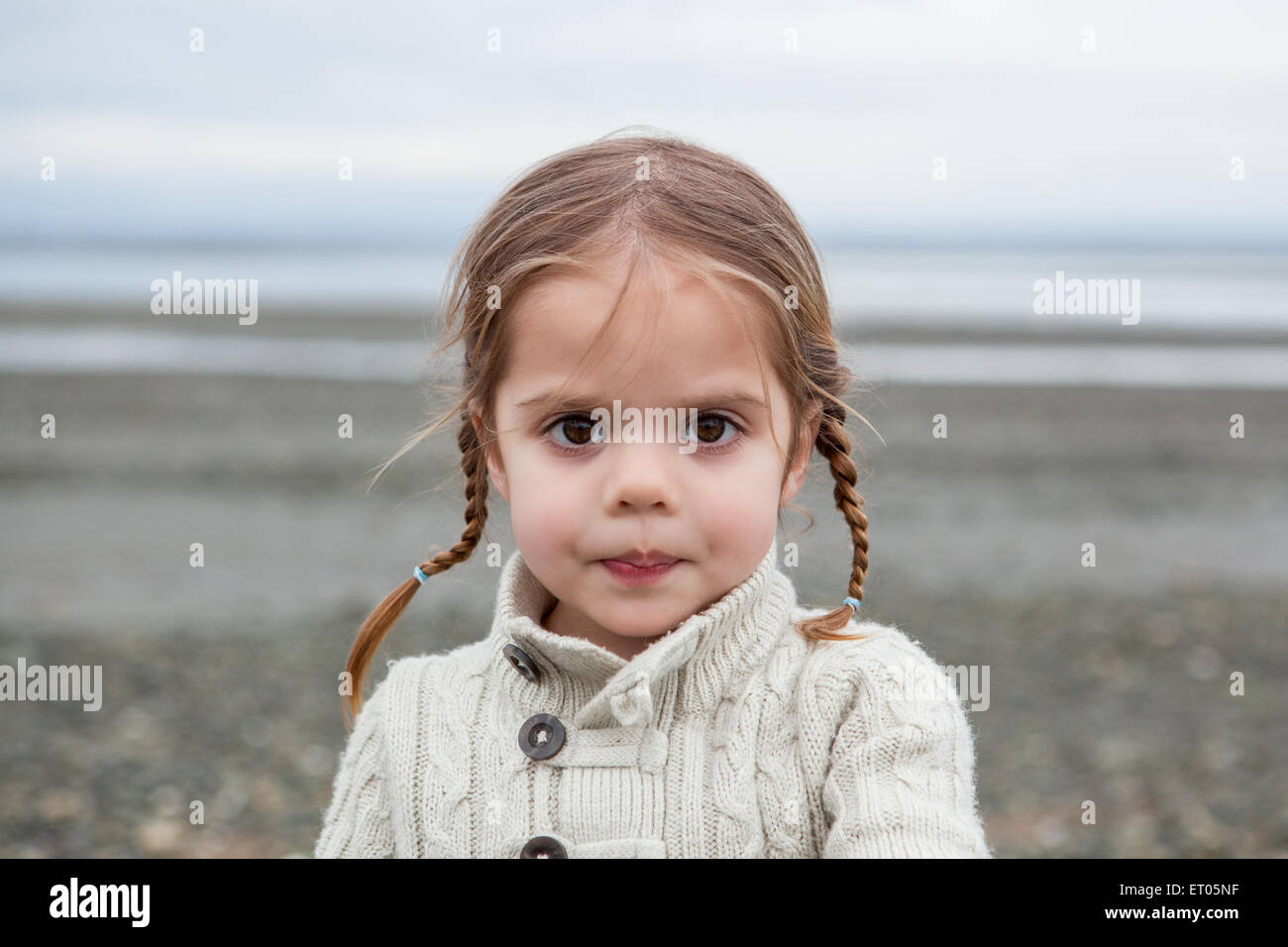 Portrait of serious girl with braided pigtails on beach - Stock Image
