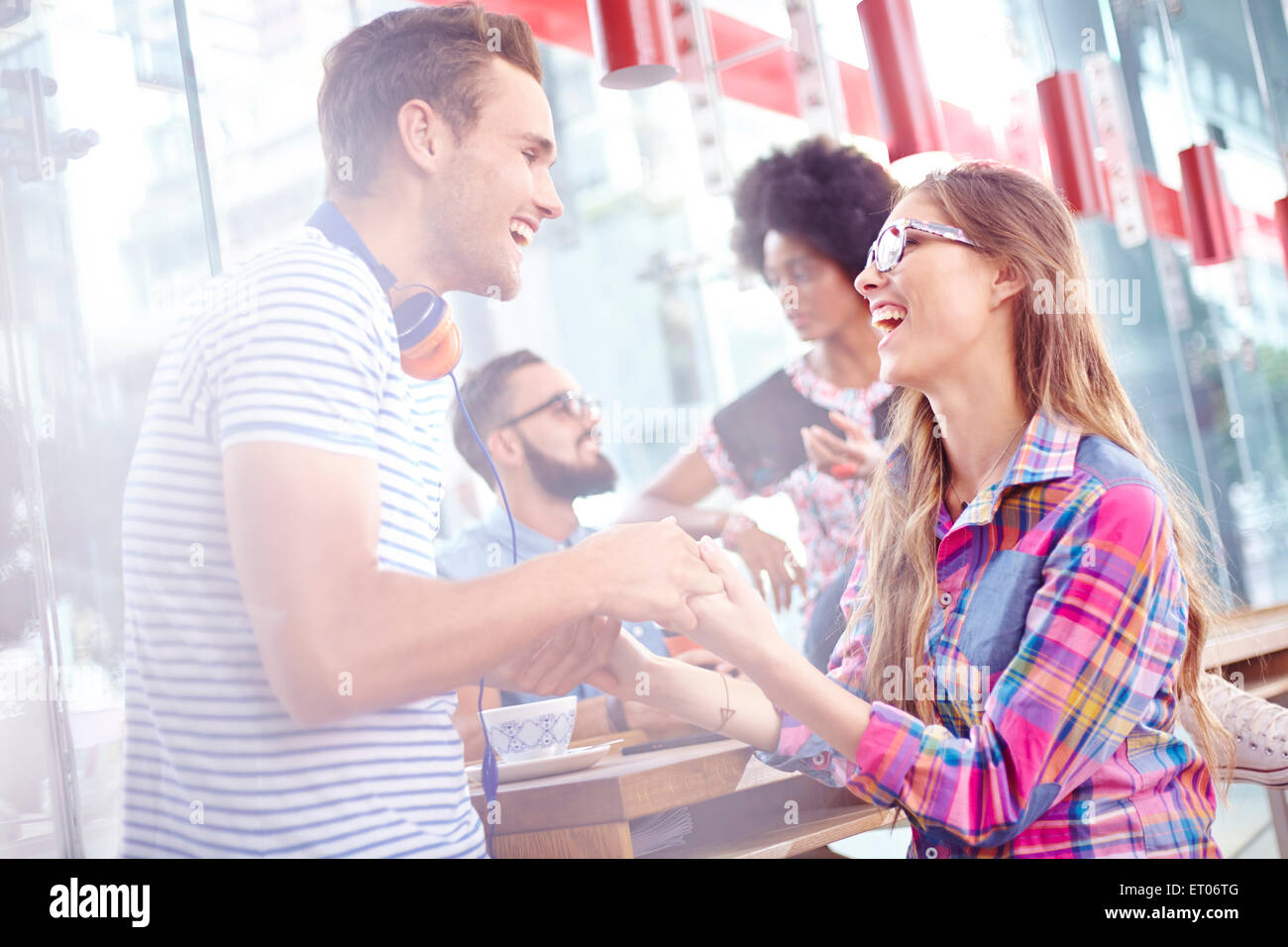 Couple laughing and holding hands in cafe - Stock Image