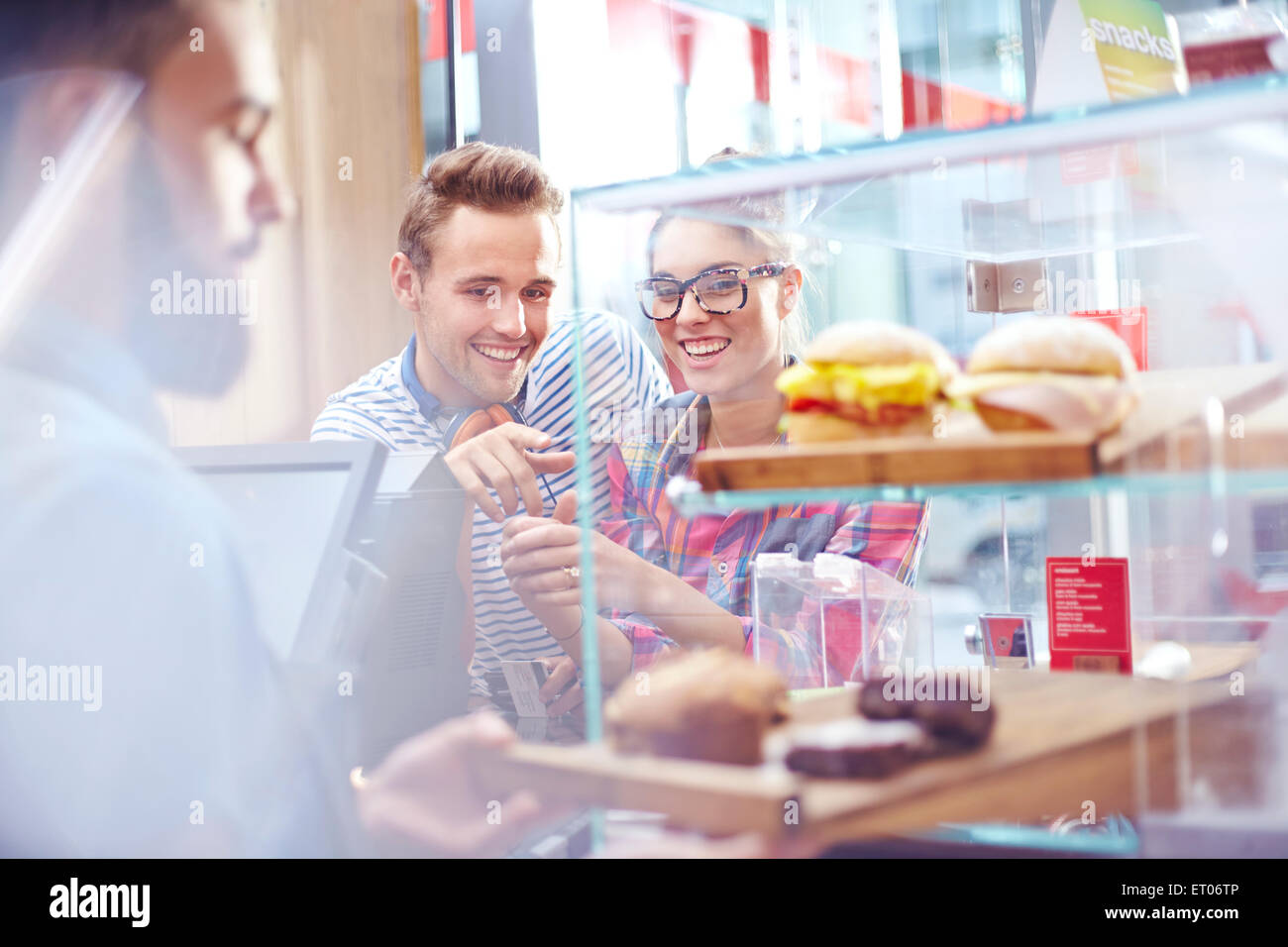 Couple choosing food at display case in cafe - Stock Image