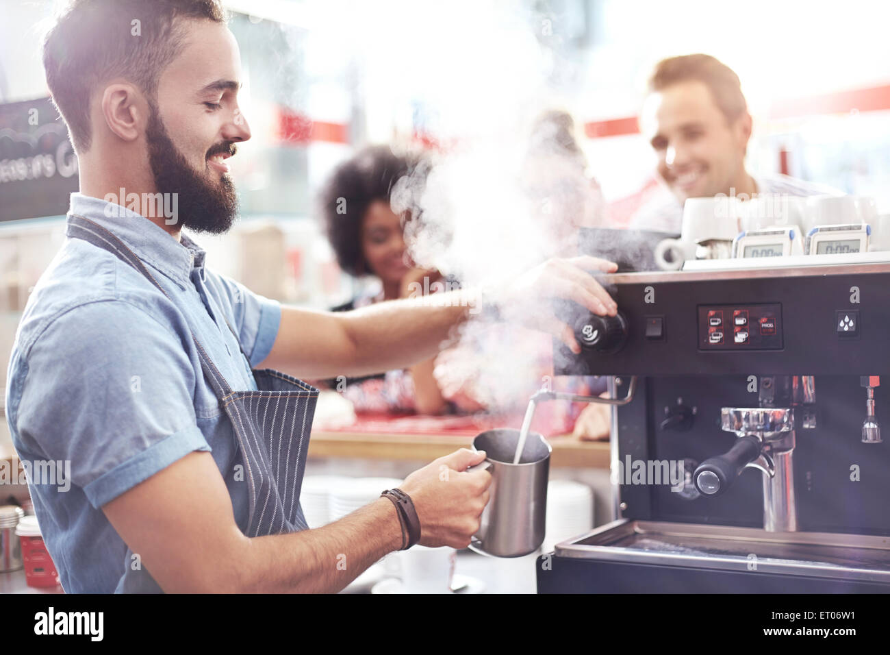 Barista steaming milk in cafe - Stock Image