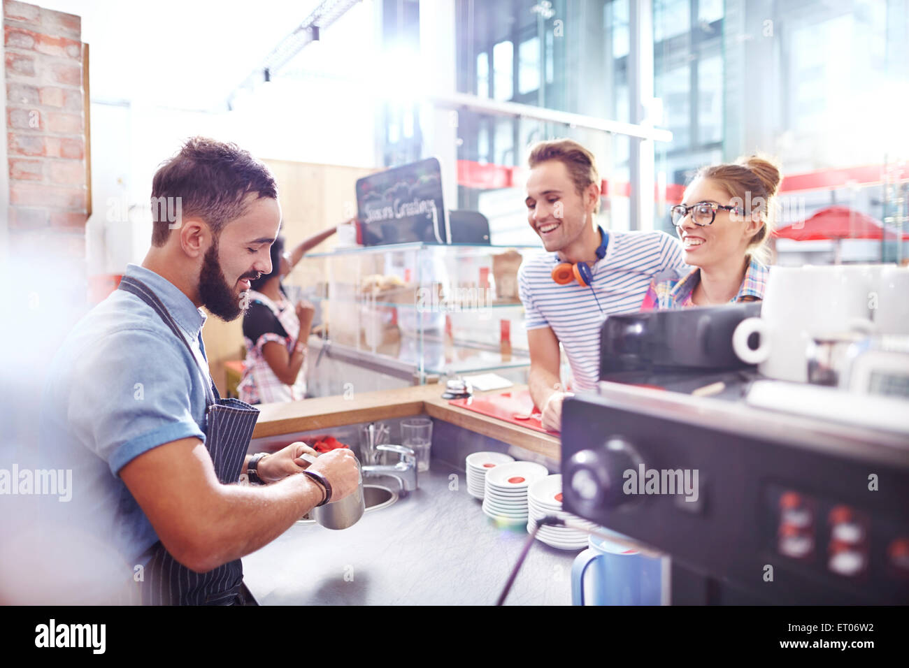 Customers watching barista make coffee in cafe - Stock Image
