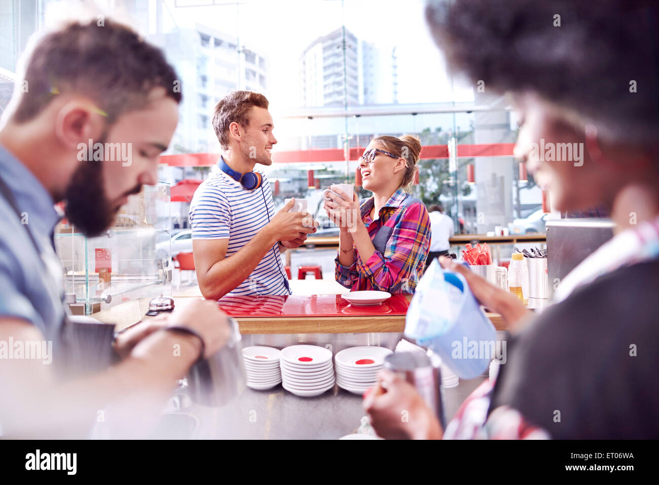 Couple talking and drinking coffee in cafe - Stock Image