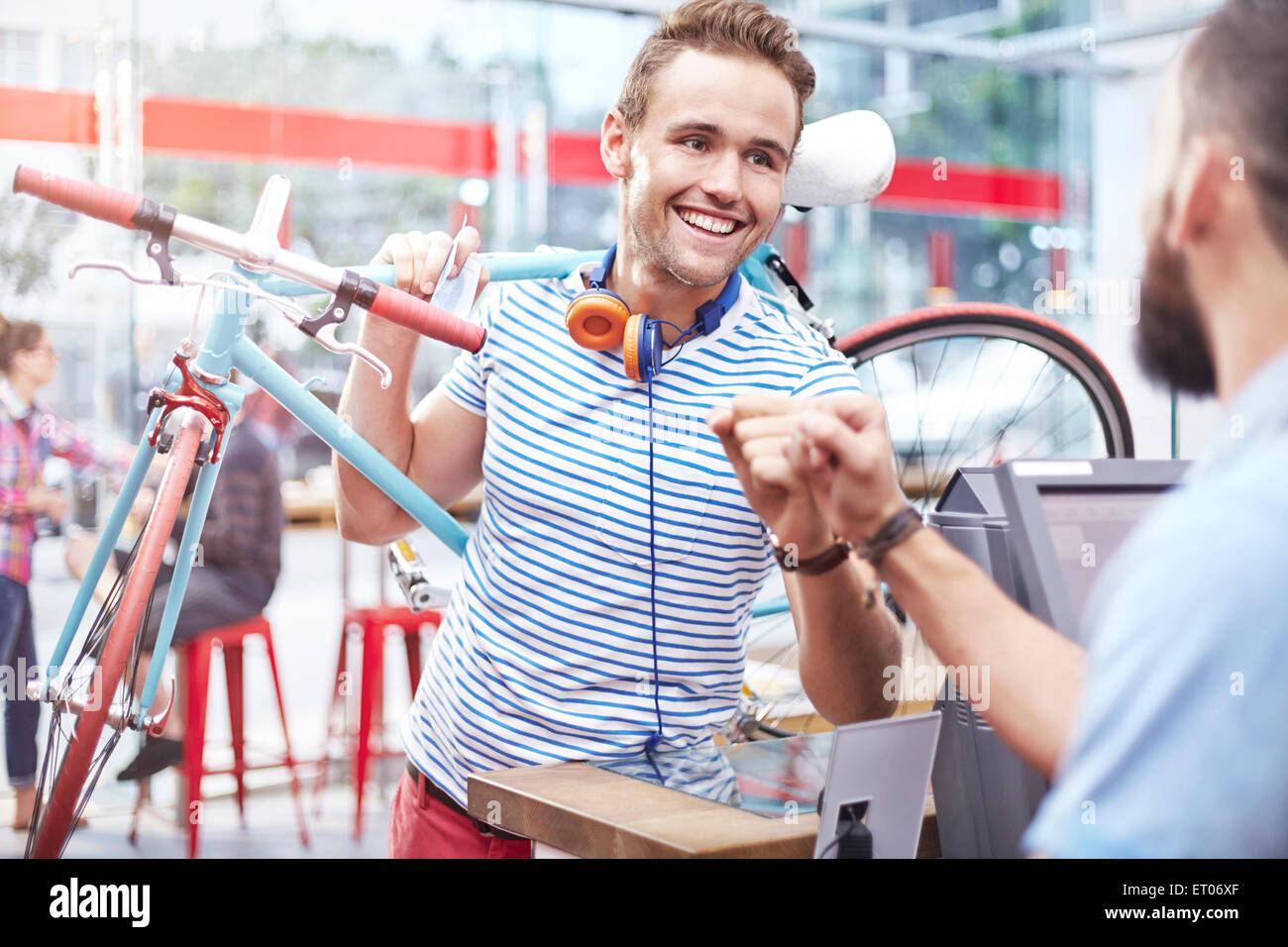 Man with bicycle fist bumping worker in cafe - Stock Image