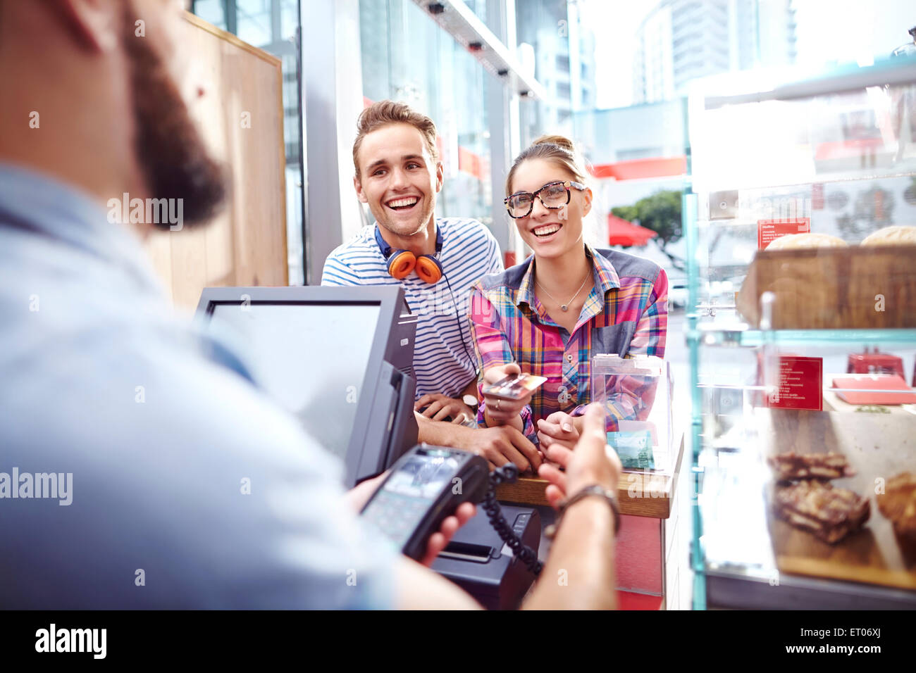 Smiling couple paying worker at cafe counter - Stock Image