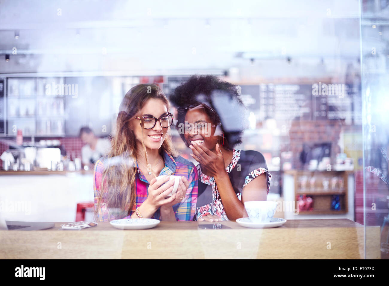 Women laughing and drinking coffee in cafe window Stock Photo