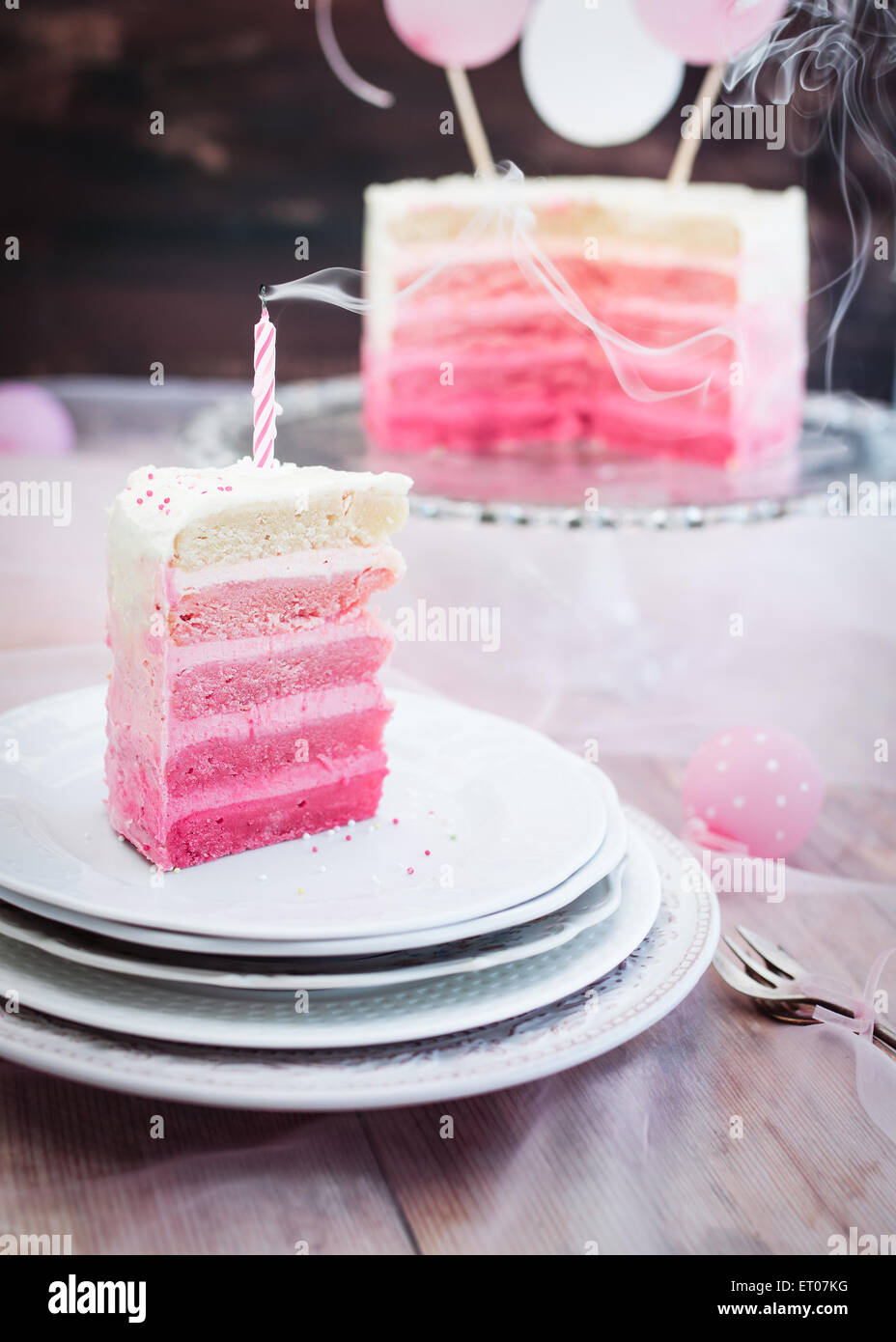 Pink and white piece of birthday cake. Selective focus. - Stock Image