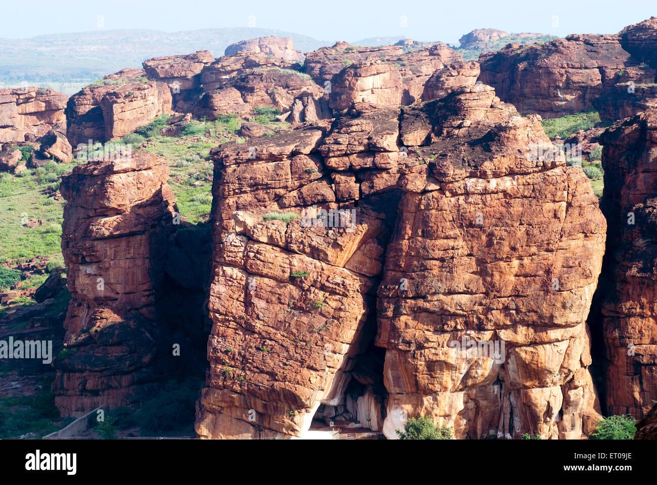 Rust red sandstone cliffs rocks in Badami ; Karnataka ; India - Stock Image