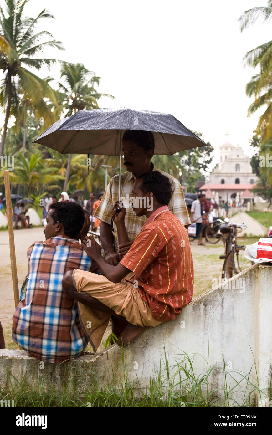 Keralites sitting near Vechoor church during a monsoon day ; Kerala ; India - Stock Image