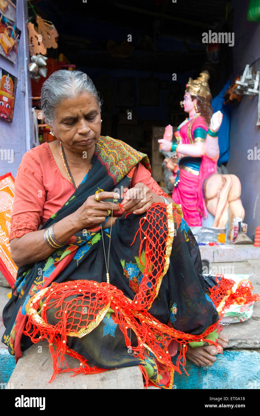 A woman weaving umbrella decorations at Bijapur ; Karnataka ; India - Stock Image