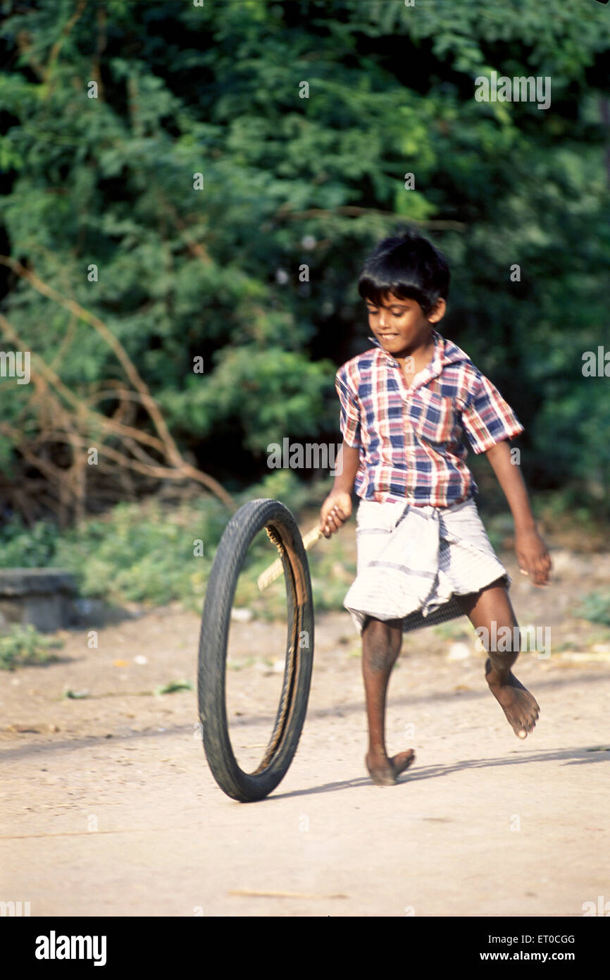 Handicapped boy playing with rubber tyre ; Tamil Nadu ; India - Stock Image
