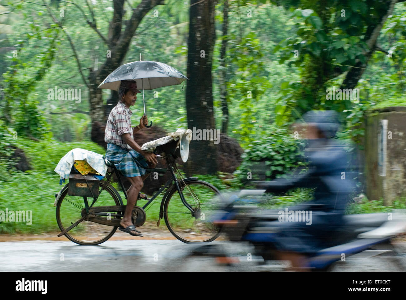 Lottery ticket seller riding bicycle with umbrella in rain ; Kerala ; India - Stock Image