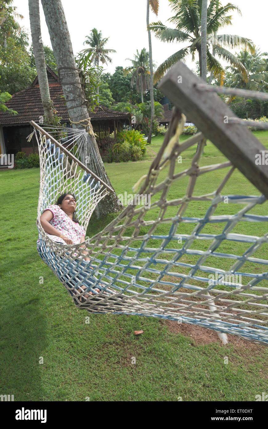 Lady resting in hammock in heritage lake resort ; Kuttanad ; Alleppey Alappuzha ; Kerala ; India MR#777L - Stock Image