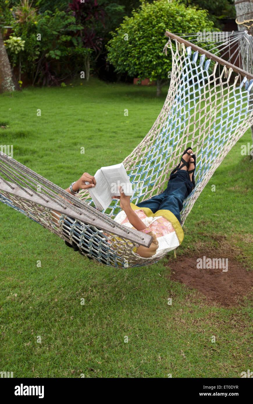 Woman reading book resting in hammock in heritage lake resort ; Kuttanad ; Alleppey Alappuzha ; Kerala ; India MR#777L - Stock Image