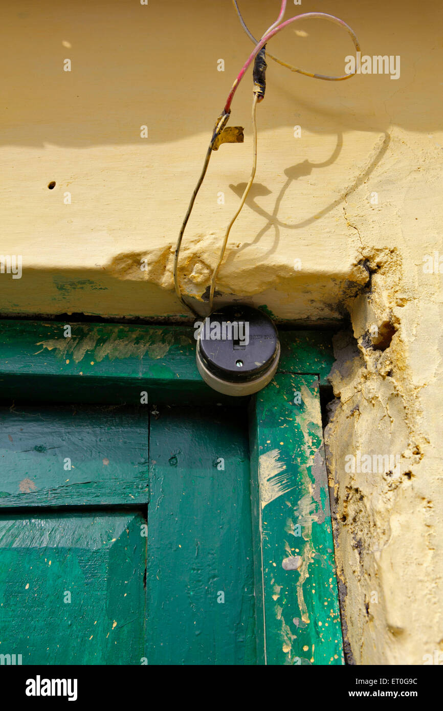 Wire dangling from old switch on green door of house ; Rajpur ; Dehradun ; Uttaranchal Uttarakhand ; India - Stock Image