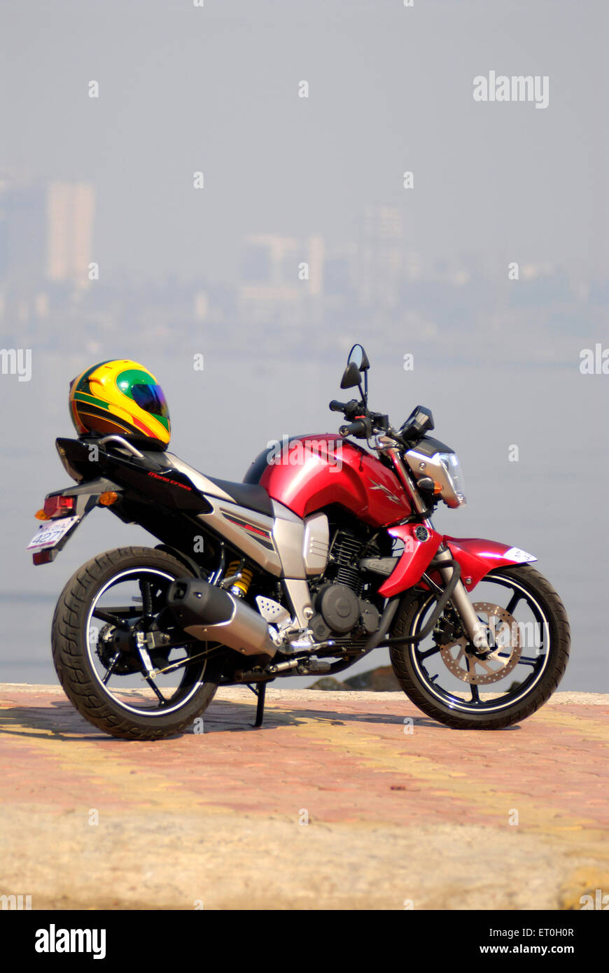 Motorcycle yamaha FZ red coloured 150cc sport bike with colourful helmet - Stock Image