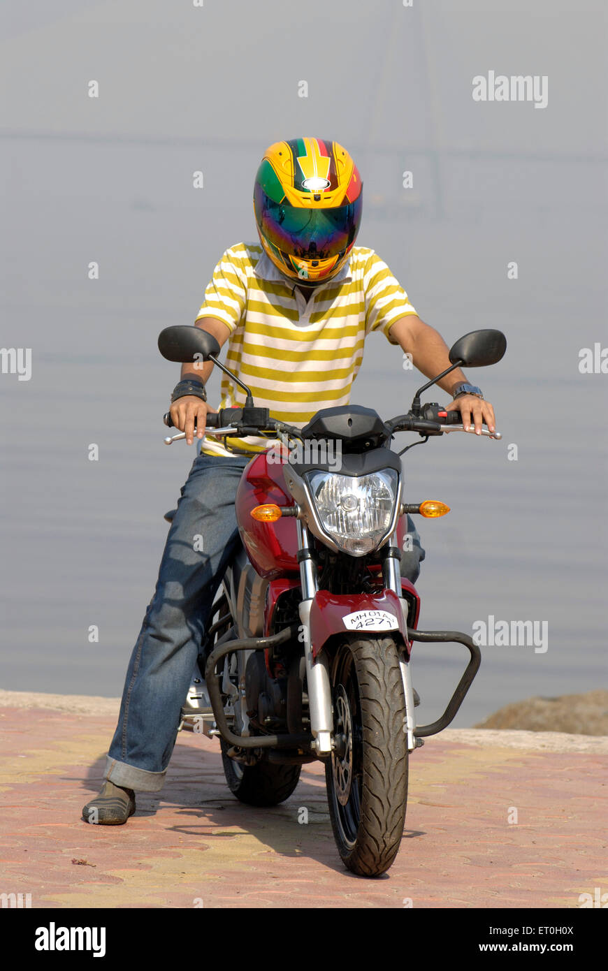 Young boy in helmet riding red coloured yamaha fz motorcycle 150cc sport bike ; Bombay Mumbai ; Maharashtra ; India - Stock Image