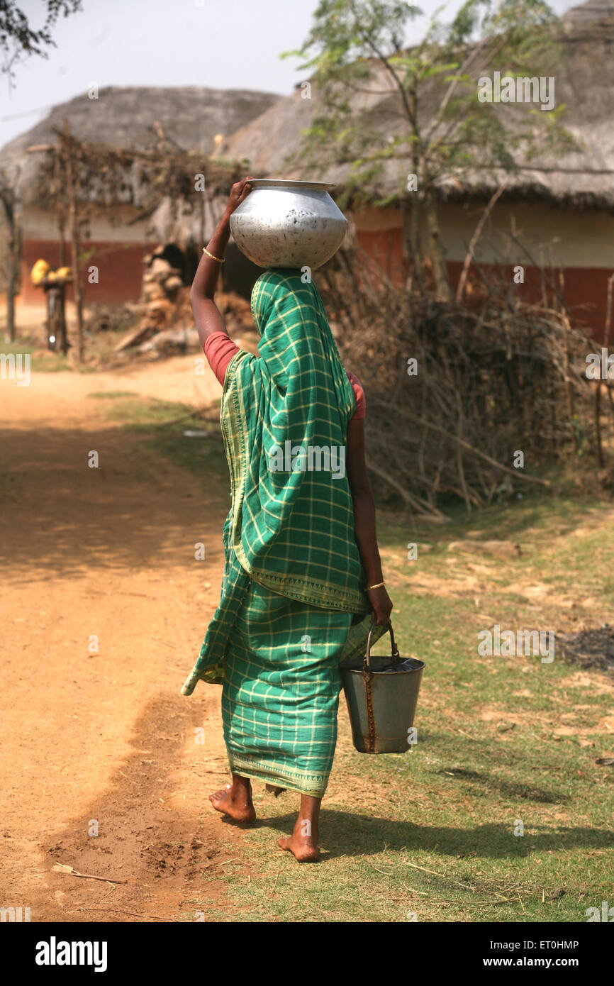 Lady carrying water pot on her head and bucket in her hand in Jharkhand ; India - Stock Image