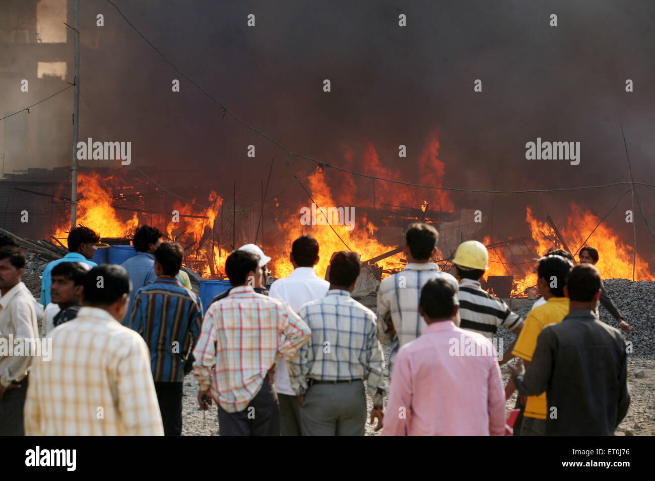 Onlookers looking at the fire at the Mhada colony in Versova ; Andheri in Bombay now Mumbai ; Maharashtra ; India - Stock Image