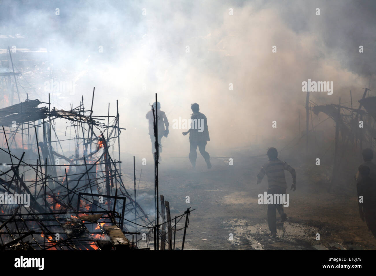 Residents trying to put off the fire which broke out at the fire at the Mhada colony in Versova ; Andheri ; Bombay - Stock Image