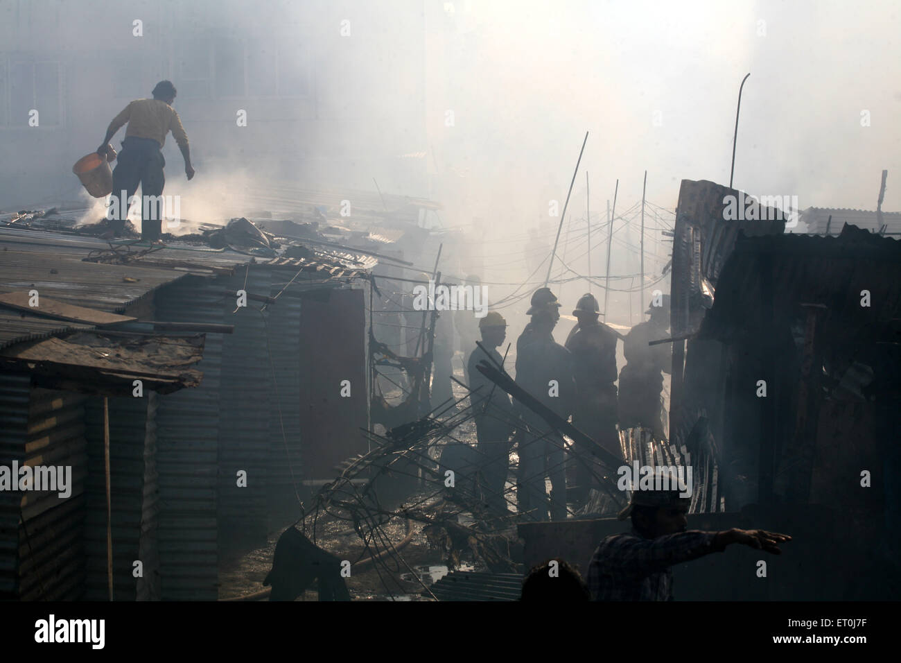 Residents along firemen trying to douse off the fire which broke mhada colony situated at Versova ; Andheri ; Mumbai - Stock Image