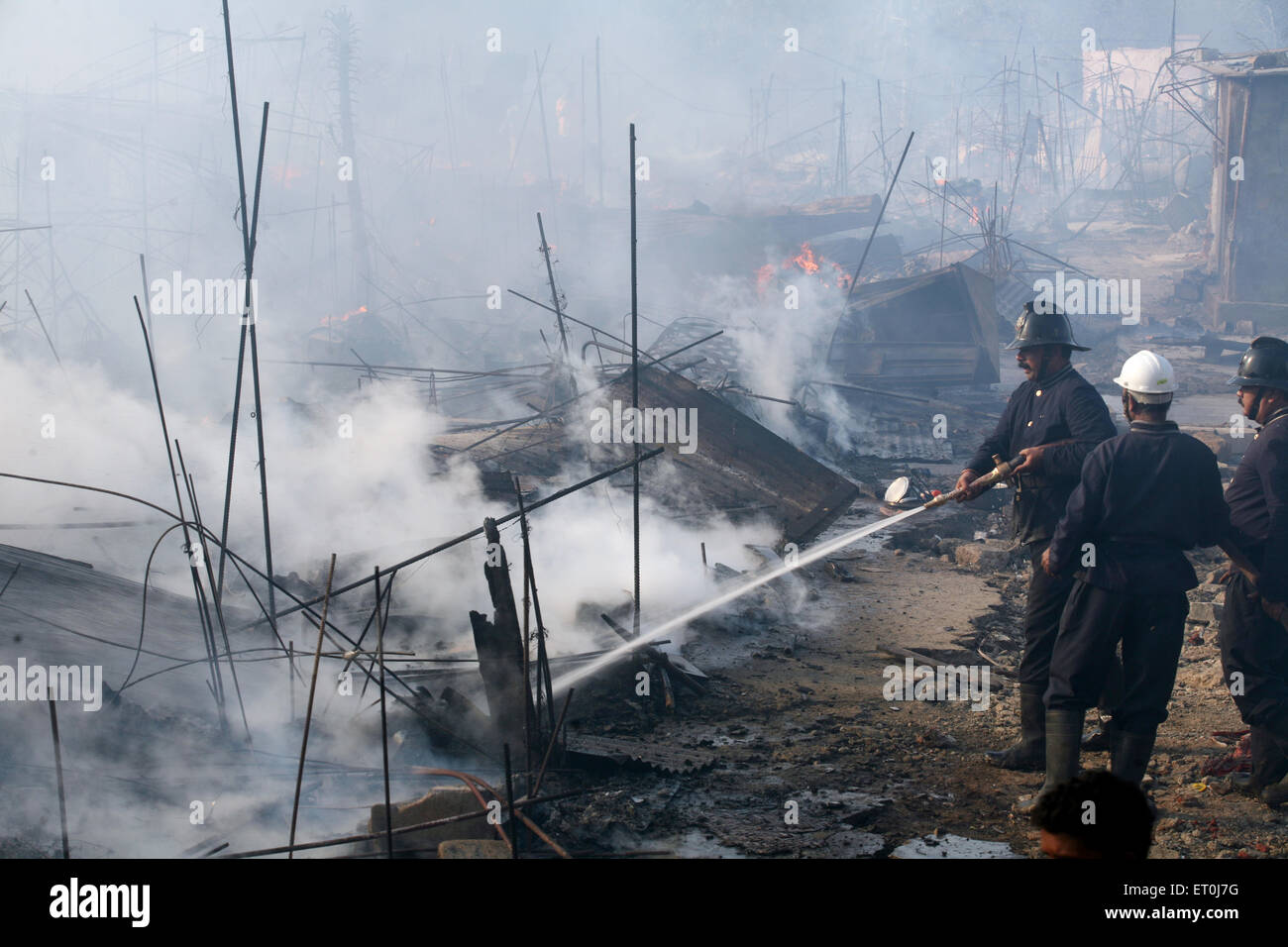 Firemen trying to douse off the fire which broke out at the Mhada colony situated at Versova ; Andheri ; Mumbai - Stock Image