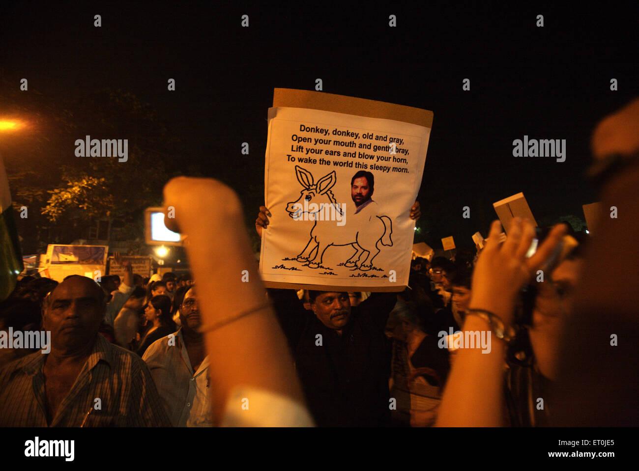 People holding placard cartoons senior BJP leader Naqvi sitting donkey mass protest terrorist attack 26th November - Stock Image