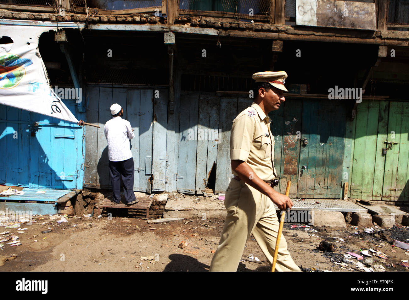 Policeman passing Shopkeeper monitoring losses property bomb blast 29 September 2008 in textile town of Malegaon - Stock Image