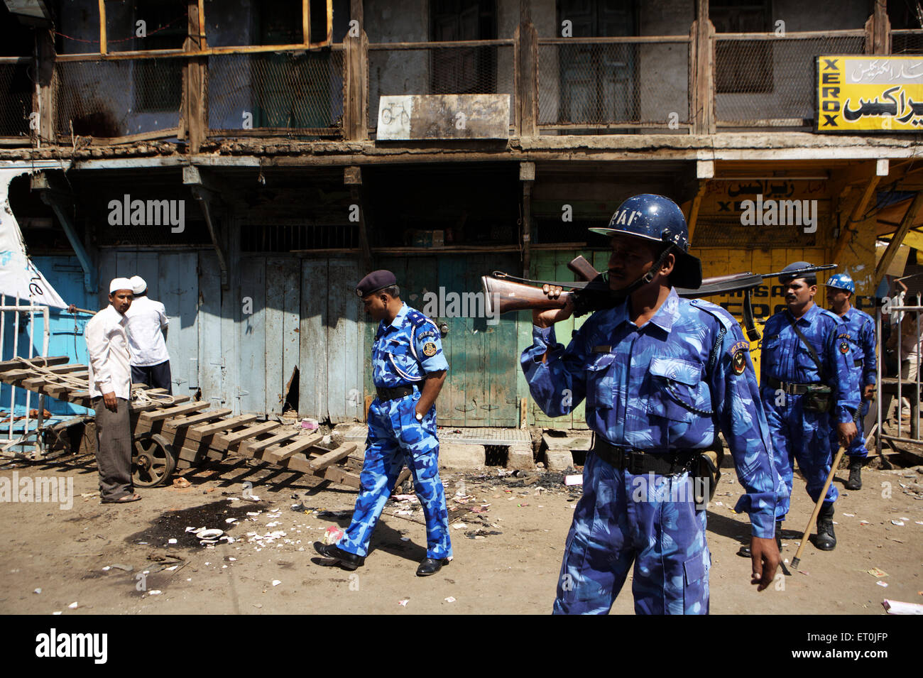 Shopkeeper monitoring losses property commandoes Rapid Action Force keeping vigil bomb blast on 29th September 2008 - Stock Image