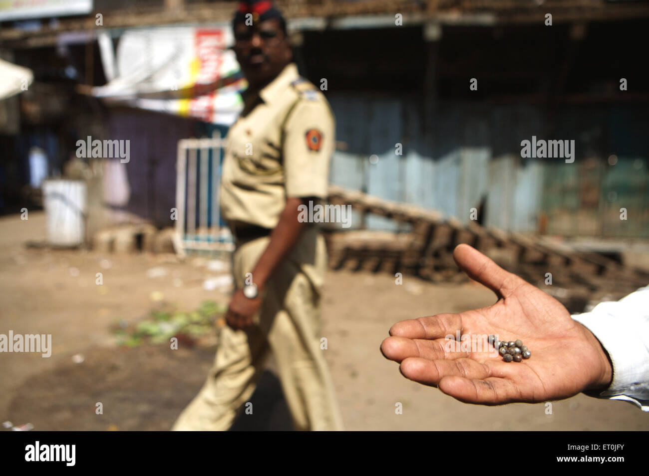 Man displaying the dismantled parts of the bomb found at the site of bomb blast which rocked textile town of Malegaon - Stock Image