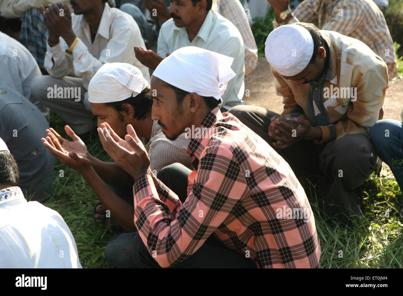 People praying during burial of their family members who died in powerful bomb blast on 29th September 2008 at Malegaon - Stock Image