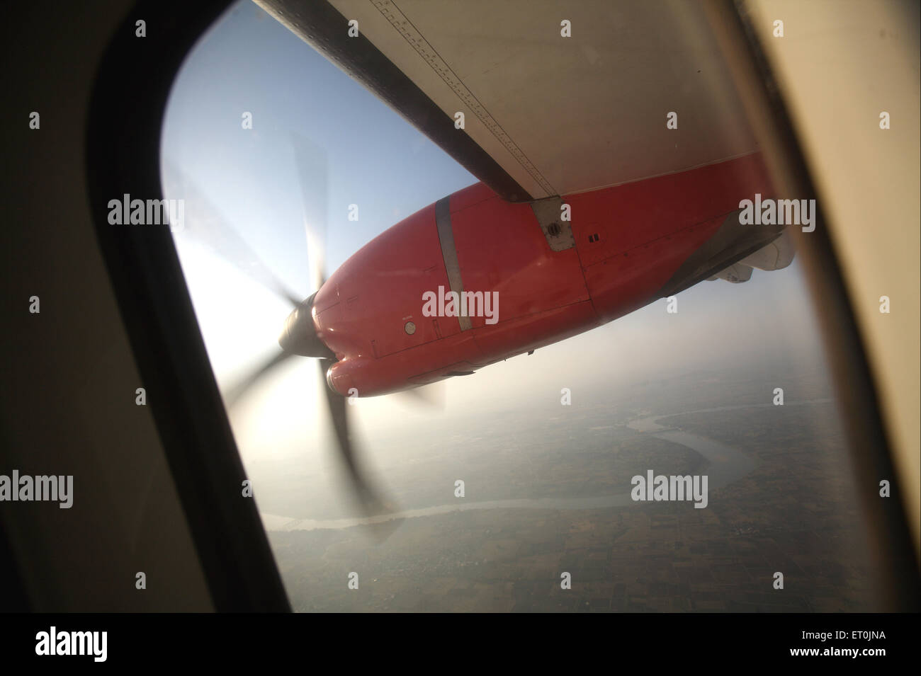 Wing of aircraft in the sky can be seen through the window ; India Stock Photo