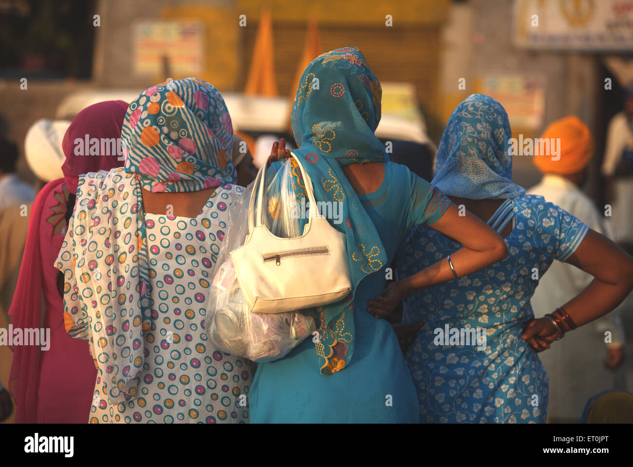 Sikh women watching daredevil stunts Nihangs Sikh warriors celebration Consecration perpetual Guru Granth Sahib - Stock Image