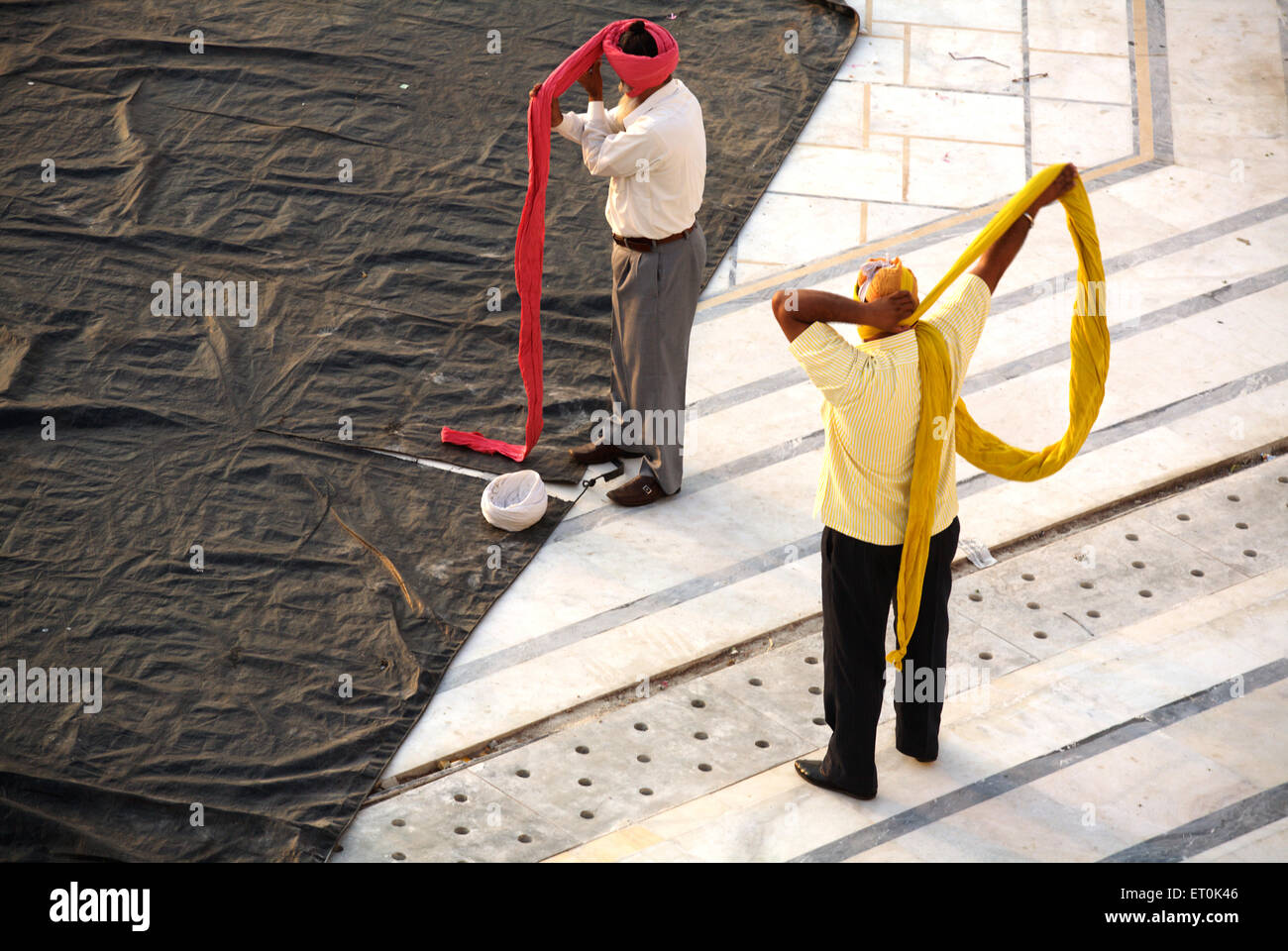 Sikh devotees tying their Pag or head gear in the compound of Sachkhand Saheb Gurudwara in Nanded ; Maharashtra - Stock Image