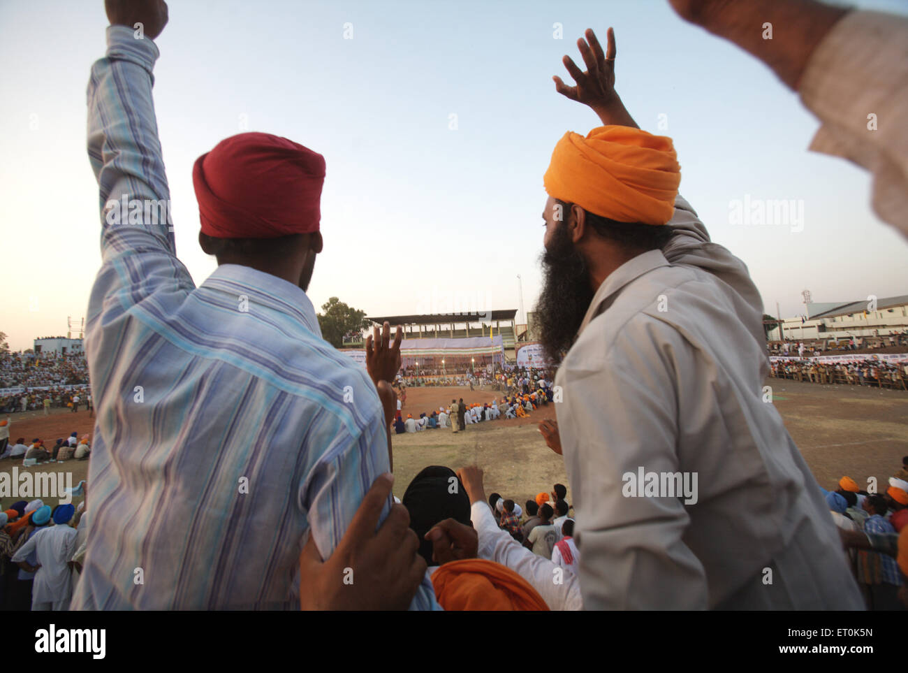 Sikh devotees encouraging players wrestling match ; perpetual Sikh Guru Granth Sahib at Khalsa Sports ground ; Nanded - Stock Image