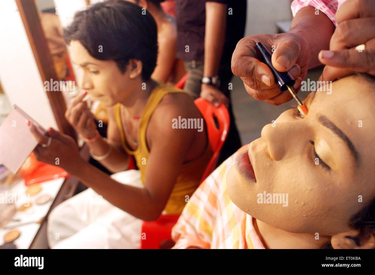 Male artist applying eye makeup and lip colors for show Bin Baicha Tamasha ; India NO MR